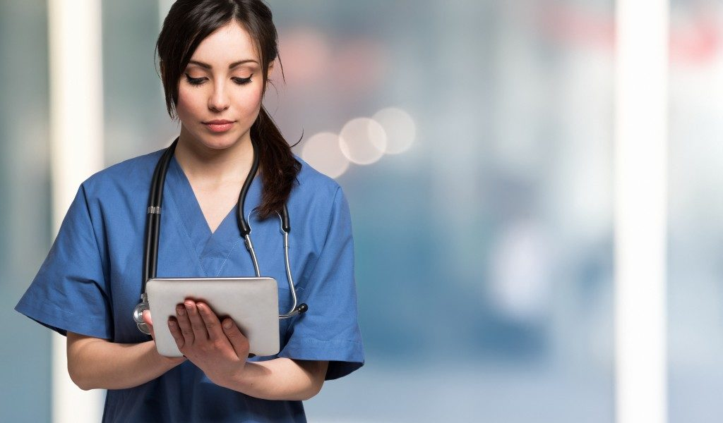 nurse using a tablet to access patient's medical information