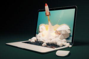 digital marketing metaphor with rocket and laptop