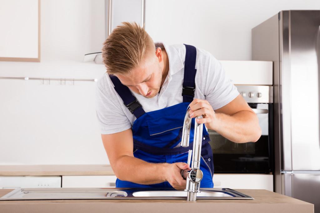 man fixing the faucet