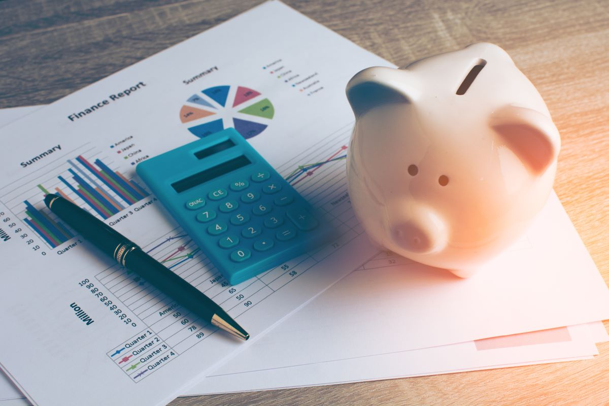 piggy bank, calculator, pen and financial report with charts
