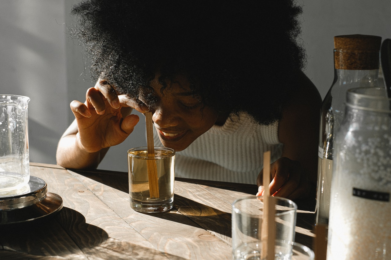 woman smelling a glass of perfume