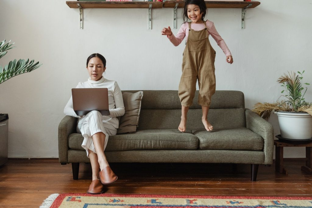 woman working on the couch with her daughter jumping next to her