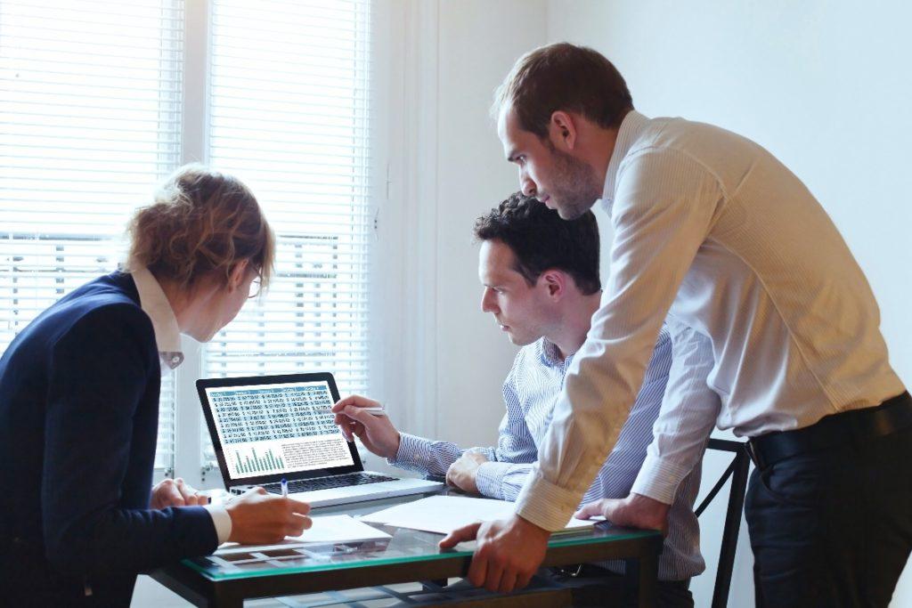 employees gathered around a laptop