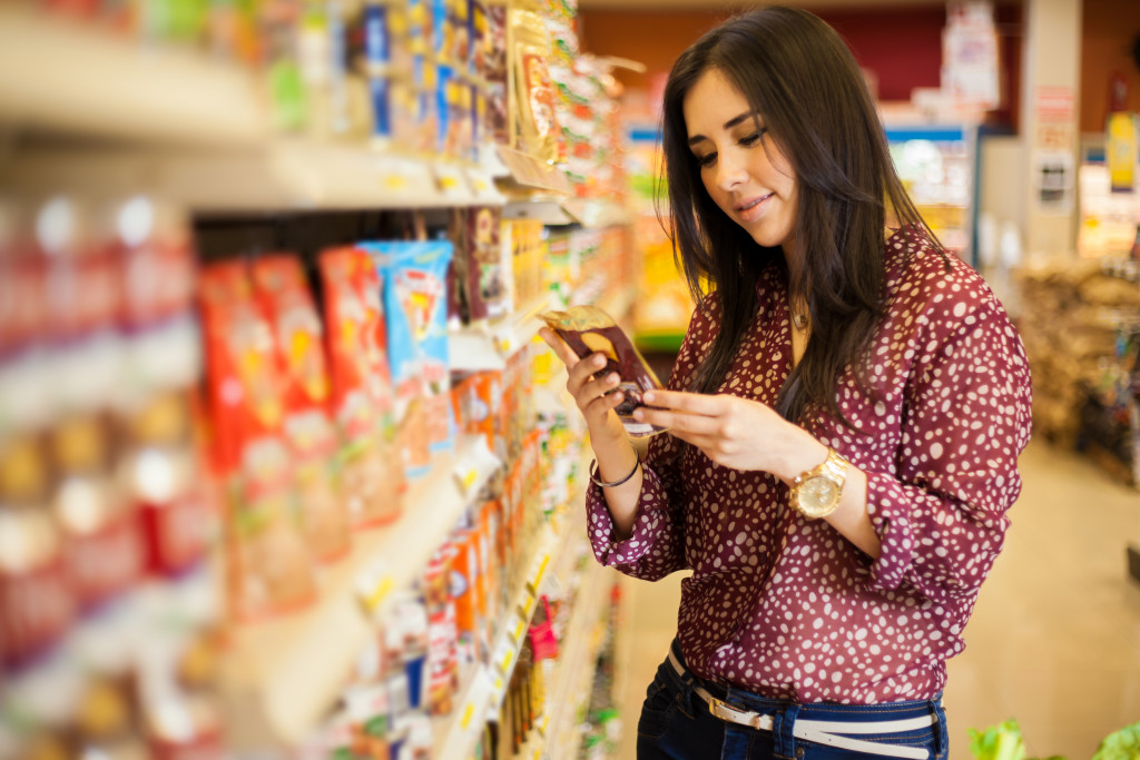 woman examining grocery store product