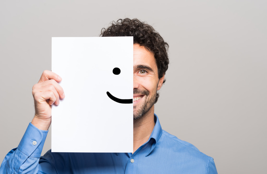 person holding a cardboard with a smiley